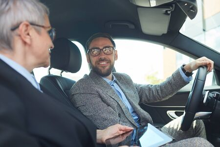 Mature bearded businessman talking to the businesswoman with tablet pc while they sitting in the car
