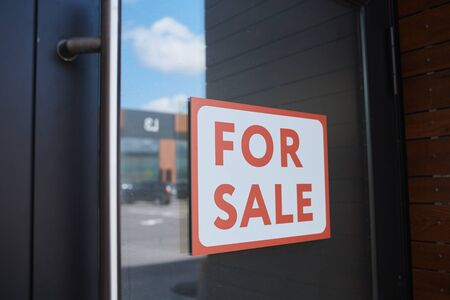 Close-up of placard For Sale hanging on the door of modern office building Standard-Bild