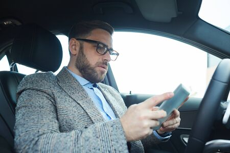 Mature bearded man using digital tablet he working online in the car