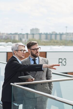 Mature businesswoman in eyeglasses pointing at something and discussing it with her colleague while they standing in the city