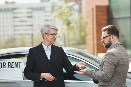 Mature businesswoman giving the keys from car to businessman who renting it they standing outdoors