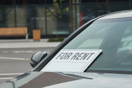 Close-up of new car with placard on the window being suggested for rent Imagens