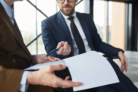 Close-up of businessman pointing at business contract and discussing details with businesswoman while they sitting at office