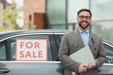 Portrait of mature bearded man holding documents and smiling at camera he buying the car