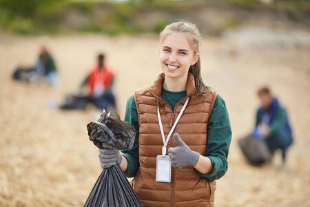 Portrait of young woman holding garbage showing thumb up and smiling at camera while standing outdoors