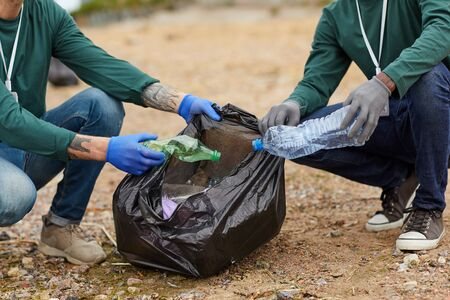 Close-up of people putting the garbage into the big black bags outdoors Stock Photo