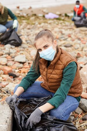 Portrait of young volunteer in protective mask sitting near the rubbish bag and looking at camera outdoors