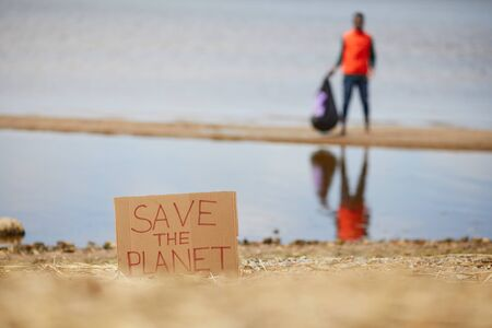 Image of placard Save the planet on the beach of the sea with man standing in the background