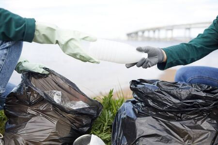 Close-up of volunteers cleaning nature from garbage they putting plastic bottles in rubbish bags