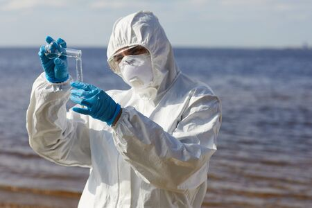Scientist in protective suit pouring liquid from one flask to another while standing near the sea outdoors Banco de Imagens