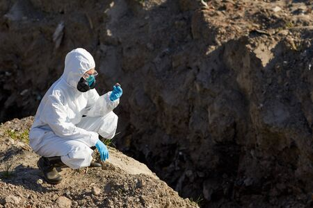 Biologist in protective suit and gloves examining the samples of rocks and stones outdoors