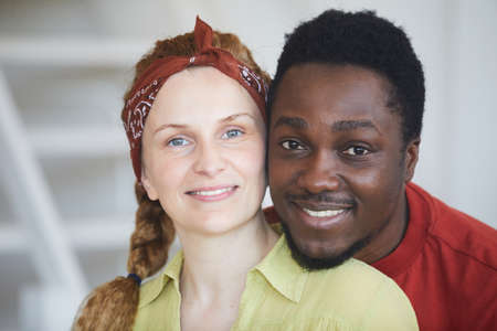 Portrait of multiracial young couple smiling at camera 免版税图像