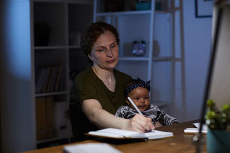 Business mother making notes in note pad while sitting at her workplace with baby she working till night Reklamní fotografie