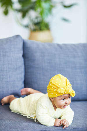 Cute African baby girl in pretty hat lying on sofa at home Reklamní fotografie