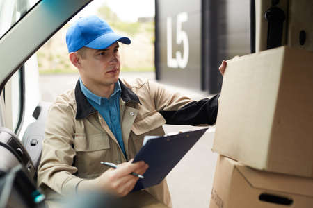 Young courier checking parcels in the van before delivering