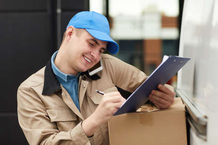 Smiling young man accepting the order by the phone and making delivery Stockfoto