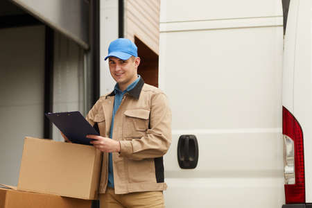 Young delivery man checking the load after delivering he standing outdoors and smiling at camera Stockfoto
