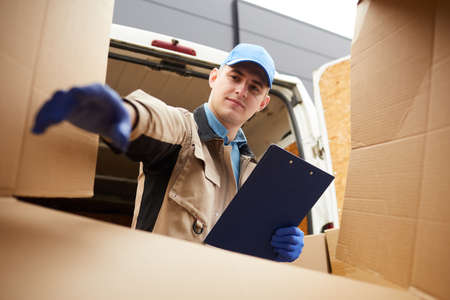 Young man in uniform with document getting something out of the cardboard box