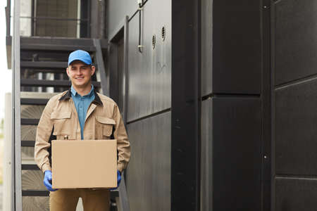 Portrait of young delivery person in uniform holding parcel and smiling at camera outdoors
