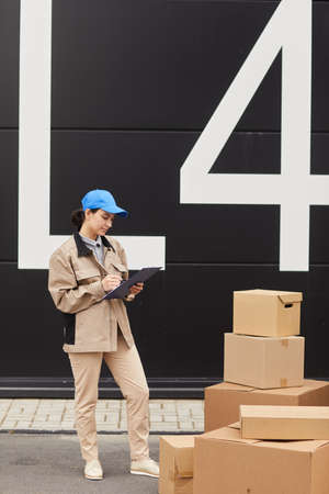 Young woman in uniform filling the document and taking the parcels while standing against the warehouse