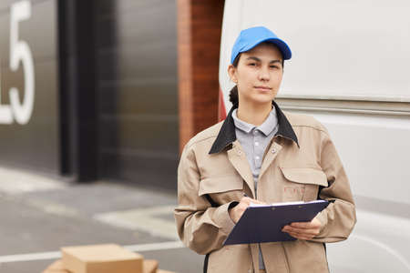 Portrait of young woman in uniform filling the form while standing outdoors she working in delivery warehouse Stockfoto