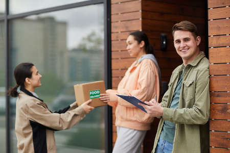 Portrait of young man smiling at camera while signing for the food delivery with courier delivering parcel in the background