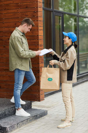 Young man signing for food delivery in document while woman giving him to his package they standing outdoors