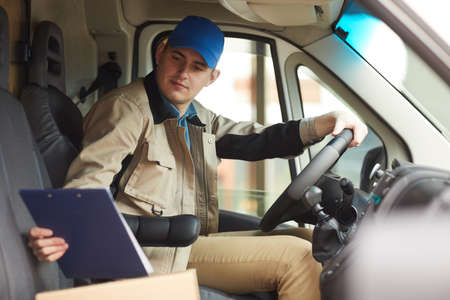 Delivery person checking the address of delivery while driving the van