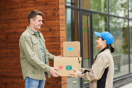 Young man getting his parcels from the courier while they standing outdoors