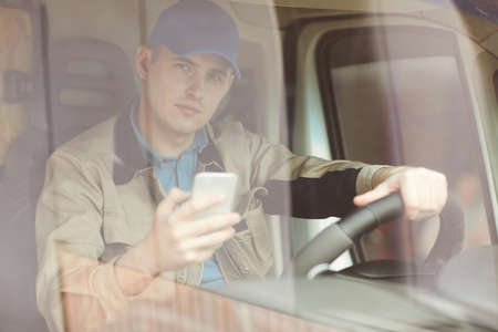Portrait of young courier sitting behind the wheel in the van and using his mobile phone 版權商用圖片