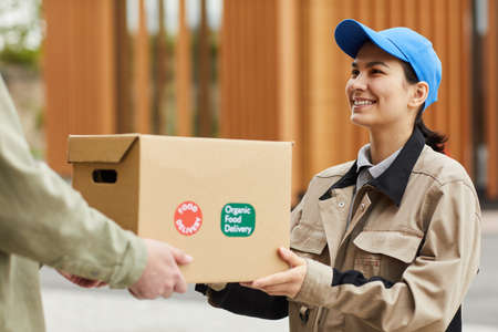 Young smiling courier in uniform delivering the parcel to man outdoors
