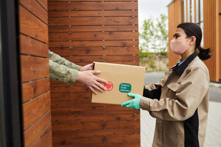 Young woman in protective mask and gloves passing the box to client she standing outdoors and delivering parcel