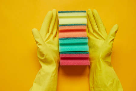 Close-up of woman in rubber gloves holding colorful sponges in a row isolated on yellow background