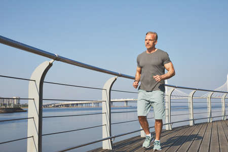 Athletic mature man in shorts jogging on city embankment in morning, healthy lifestyle concept