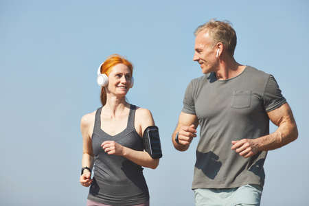 Smiling attractive redhead woman with armband enjoying jogging with boyfriend in morning