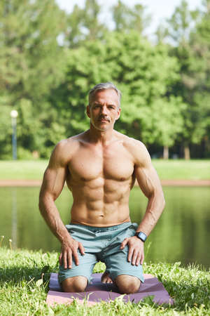 Portrait of confident muscle-bound man with gray hair sitting on exercise mat in park with lake