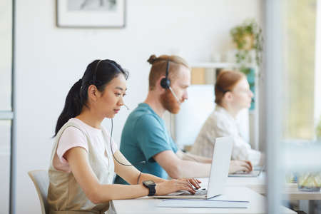 Group of business people in headphones sitting at the table and working on laptop computers at office