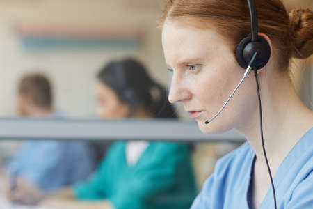 Close-up of female operator in headphones concentrating on her work in call center Banque d'images