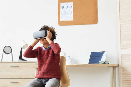 African boy in VR glasses sitting on chair and enjoying the virtual game after lessons at home