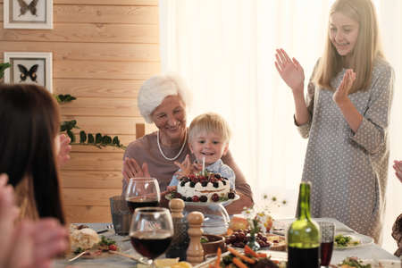 Little boy sitting on the knees of his grandmother and blowing candle on the cake while his family congratulating him with birthday Archivio Fotografico