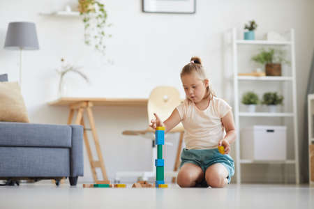 Girl with down syndrome sitting on the floor in the room and building a tower from colored blocks Banque d'images