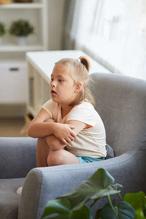 Little girl with down syndrome sitting on armchair and resting in the living room