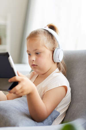 Little girl with down syndrome wearing headphones and watching cartoons on digital tablet while sitting on sofa in the room Archivio Fotografico