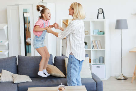 Girl with down syndrome jumping on the sofa she playing with her mother while they are at home