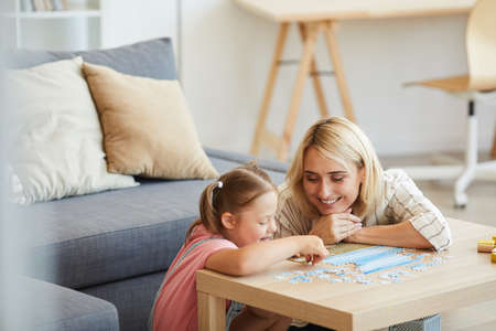 Young happy mother teaching her daughter with down syndrome collecting puzzles at the table in the living room