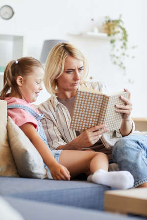 Young woman sitting on sofa and reading a book to girl with down syndrome in the room