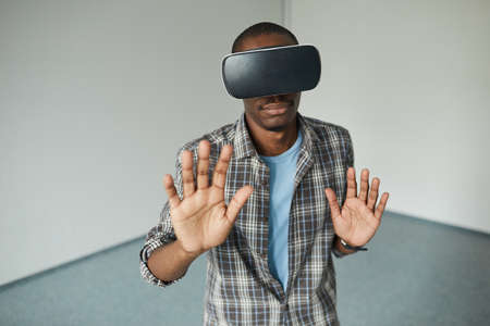 African young man in virtual reality goggles gesturing during the game he is in empty room