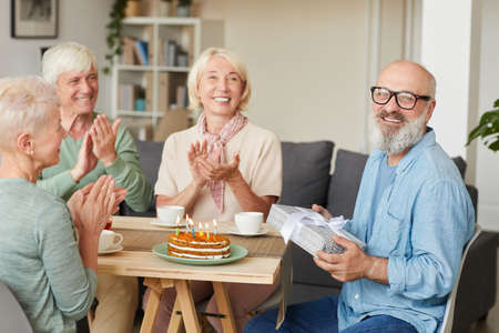 Portrait of senior bearded man holding gift box and smiling at camera while his friends congratulating him at the table
