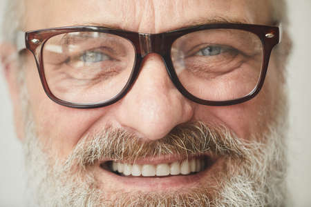 Close-up of senior bearded man in eyeglasses smiling at camera