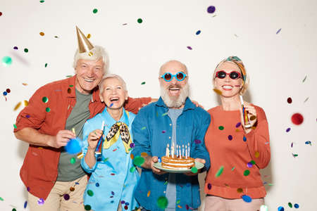 Portrait of group of senior people with birthday cake standing under the confetti and smiling at camera against the white background
